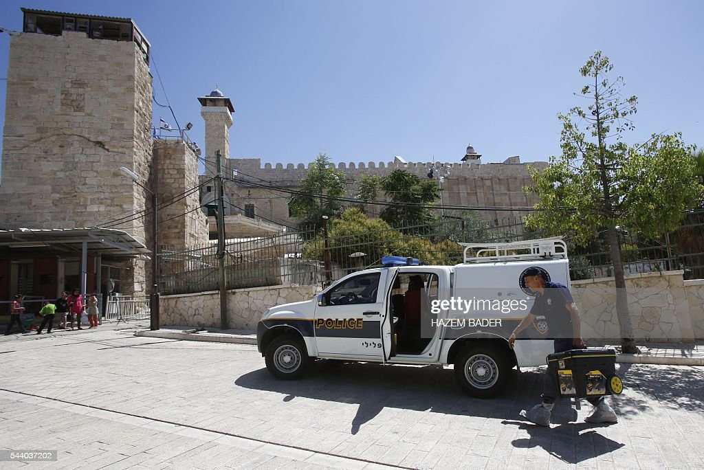 An Israeli forensic policemen carries his tools on July 1, 2016 near the entrance of a religious site known to Muslims as the Ibrahimi Mosque and to Jews as the Cave of the Patriarchs, in the flashpoint West Bank city of Hebron, after a Palestinian woman attempted to stab an Israeli guard and was shot dead at the site, according to Israeli police. It was the third violent incident in Israel and the Palestinian territories in two days and came as Muslims neared the end of their holy fasting month of Ramadan. BADER