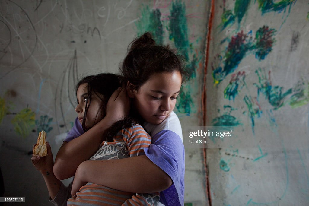 An Israeli girl holds her sister as they take cover in a large concrete pipe used as a bomb shelter during a rocket attack from the Gaza Strip on November 19, 2012 in Nitzan, Israel. According to reports November 19, 2012, at least 90 Palestinians have been killed and more than 700 wounded during the Israeli offensive in the Gaza Strip.