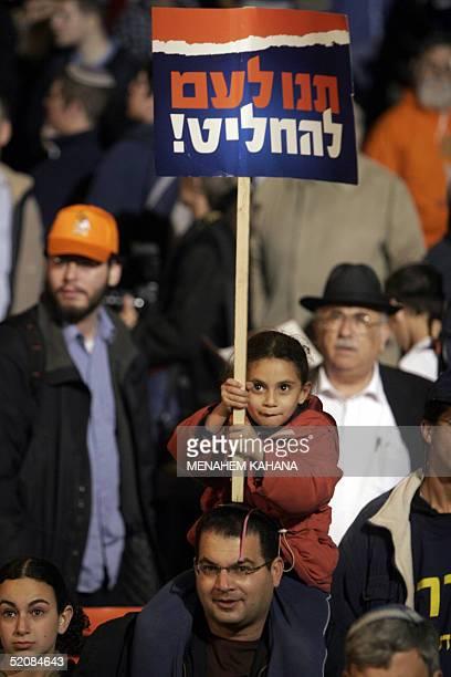 An Israeli girl holds up a banner calling for a referendum as Israeli rightwing demonstrators protest outside Israeli Prime Minister Ariel Sharon's...