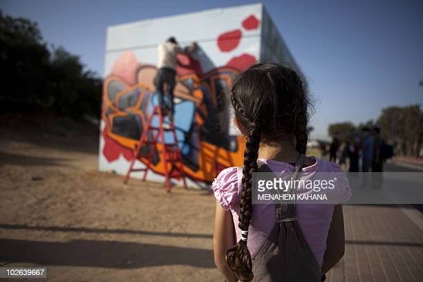 An Israeli girl looks at a graffiti artist spraypainting a bomb shelter in the southern Israeli town of Sderot neighbouring the Gaza Strip on April...