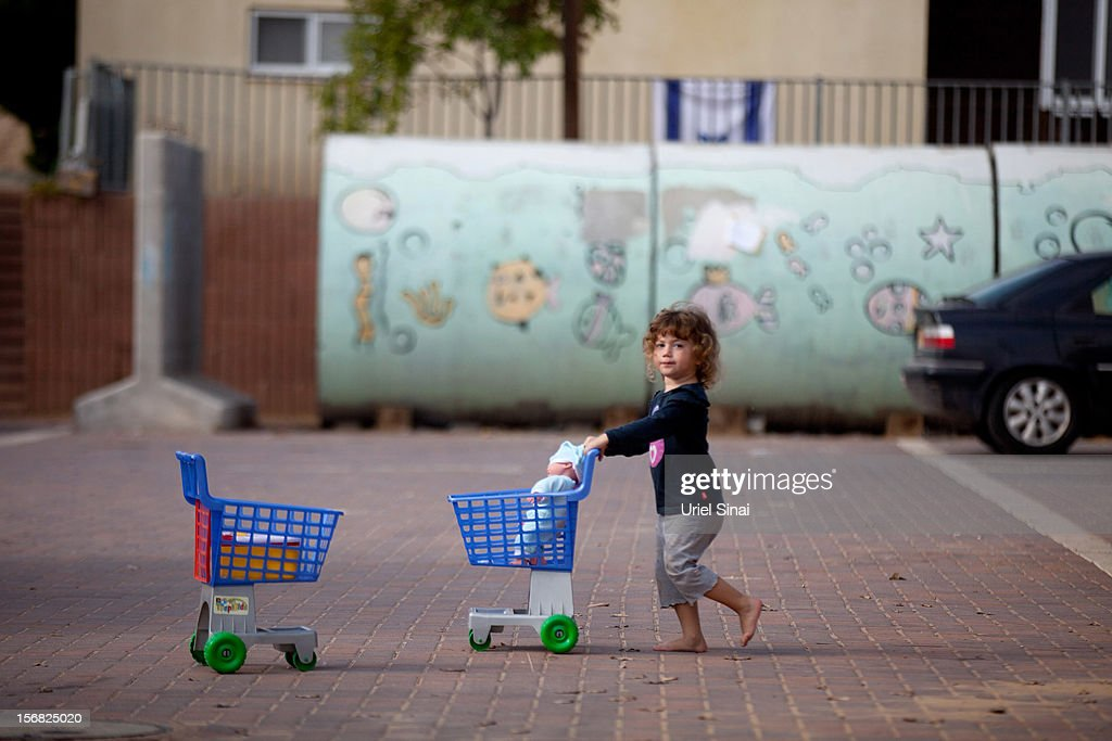 An Israeli girl plays outside her house and next to a large concrete pipe used as a bomb shelter on November 22, 2012 in Nitzan, Israel. The ceasefire between Israel and Hamas appears to be holding despite rockets being fired from Gaza. During the night the IDF reportedly arrested a number of 'terror operatives' in the West Bank in continued efforts to restore peace in the region.