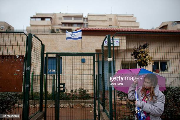 An Israeli girl shelters under an umbrella on December 4 2012 in the West Bank Jewish settlement of Ariel Israel plans to build 3000 new settler...
