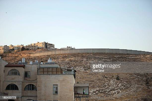 An Israeli girl stands on her balcony near the Israeli West Bank barrier in the Neve Yaakov neighborhood on September 12 2013 in East Jerusalem West...
