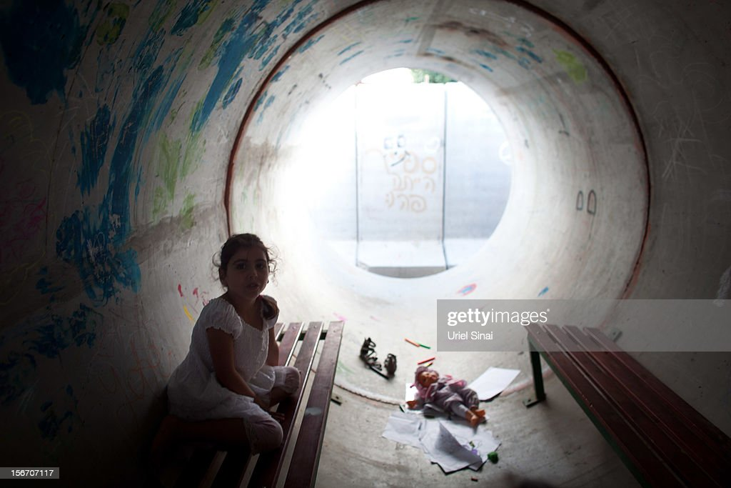 An Israeli girl takes cover in a large concrete pipe used as a bomb shelter during a rocket attack from the Gaza Strip on November 19, 2012 in Nitzan, Israel. According to reports November 19, 2012, at least 90 Palestinians have been killed and more than 700 wounded during the Israeli offensive in the Gaza Strip.