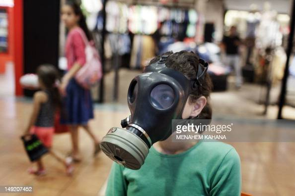 An Israeli girl tries a gasmask at a distribution center in a shopping center in Mevaseret Zion on the outskirts of Jerusalem on July 25 2012 Israel...