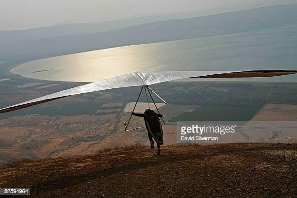 An Israeli hangglider launches himself from the cliffs looming over the Sea of Galilee to catch the thermals rising from the water during the Holy...