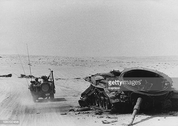 An Israeli jeep passes a knockedout Arab tank on the west Suez Canal front in the Egyptian Sinai Desert during the Yom Kippur War 24th October 1973