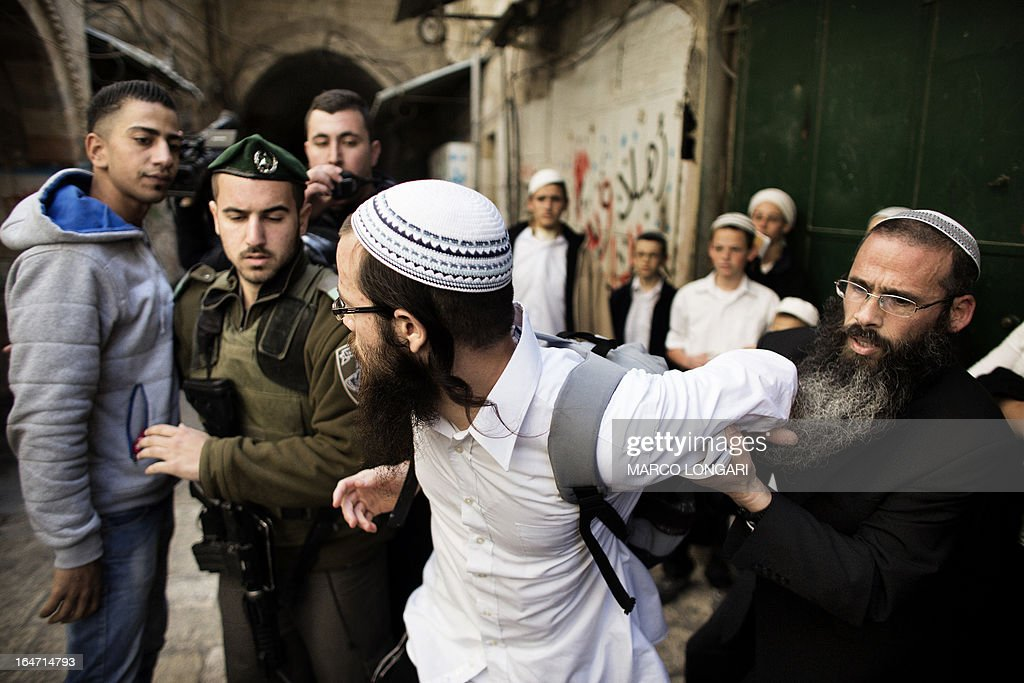 An Israeli Jew is restrained by a fellow worshiper during a dispute with a Palestinian man as they leave the Temple Mount, known to the Palestinians as the al-Aqsa compound, in Jerusalem on March 27, 2013. Israeli police stopped far-right member of parliament, Moshe Feiglin, from entering the flashpoint holy site in Jerusalem fearing a violent response from Muslims at the site.