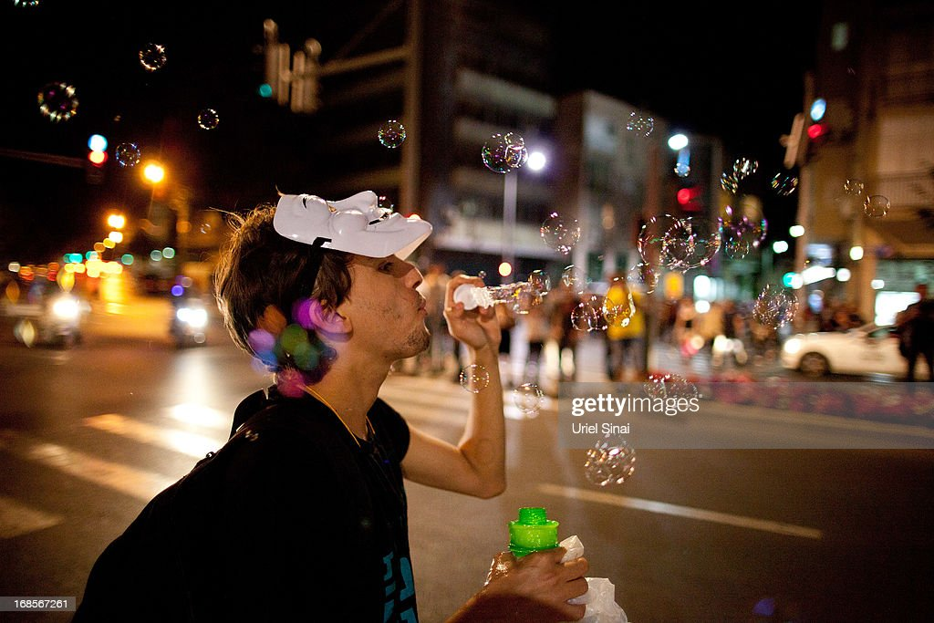 An Israeli man blows bubbles as demonstrators march through the streets to protest against Israeli Finance Minister Yair Lapid's budget cuts on May 11, 2013 in Tel Aviv, Israel. Thousands of Israelis took to the streets to protest against austerity measures presented this week as part of the state's new budget.