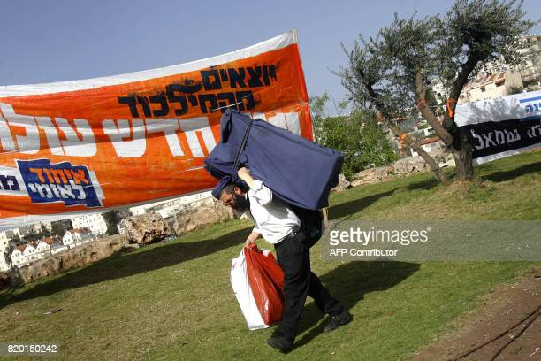 An Israeli man carries a rolledup election banner which he plans to setup in Jerusalem 23 March 2006 less than a week away from the country's 17th...