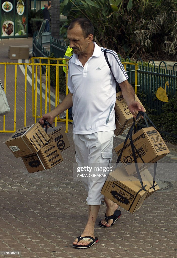 An Israeli man carries boxes containing gas masks after collecting them from a distribution centre in the northern Israeli city of Kiryat Motzkin, near the Mediterranean coastal city of Haifa on September 1, 2013, as tension surrounding the Syrian crisis escalated. A Western bombing blitz against Syria had appeared imminent earlier this week but US President Barack Obama has postponed threatened missile strikes in a risky gamble that he can win more support for his plan to punish Bashar al-Assad's regime.