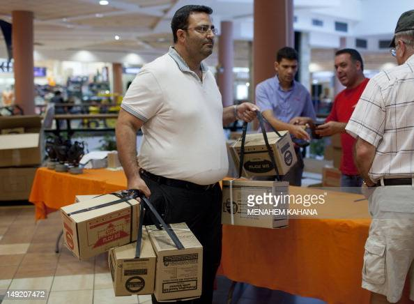An Israeli man carries boxes with gas masks at a distribution center in a shopping center in Mevaseret Zion on the outskirts of Jerusalem on July 25...