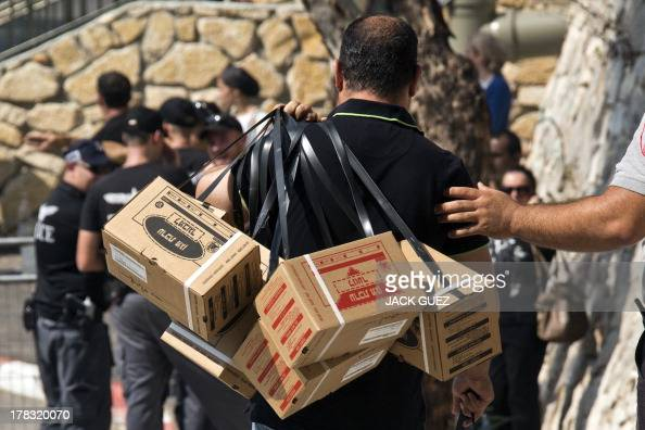 An Israeli man carries gas mask kits as he leaves a distribution center in the Mediterranean coastal city of Haifa northern Israel on August 29 2013...