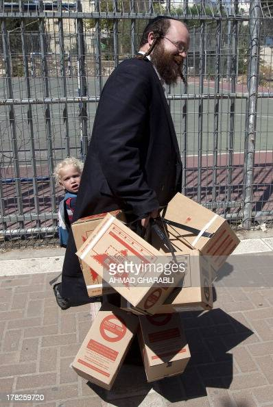 An Israeli man carries gas mask kits near his son as he leaves a distribution point in Jerusalem on August 28 2013 Fearing the fallout of a possible...