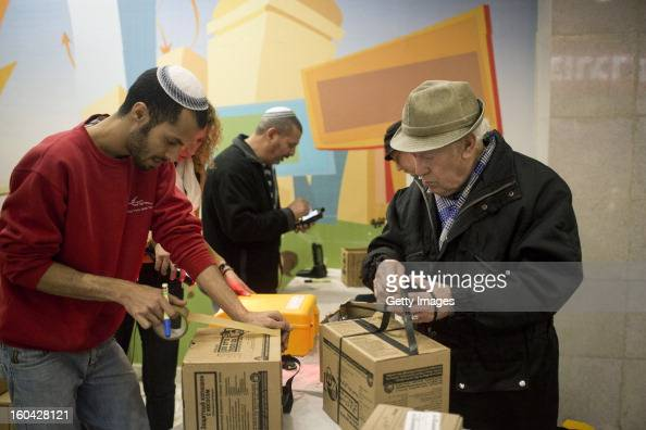 An Israeli man collects gas mask kits from a distribution station in a mall January 31 in Pisgat Ze'ev East Jerusalem Israel Israel remains on high...