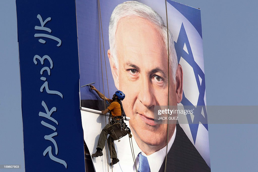 An Israeli man hangs a campaign poster for Israeli Prime Minister Benjamin Netanyahu in Tel Aviv on January 17, 2013. Thirty-eight parties on 34 lists will battle for seats in the next Knesset, reflecting the country's eclectic political map. Placard reads in Hebrew 'I need you.'