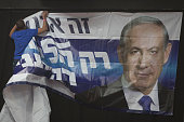 An Israeli man hangs a poster of Prime Minister Benjamin Netanyahu at his election campaign headquarters on election day on March 17 2015 in Tel Aviv...