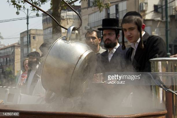 An Israeli man immerses cooking pots into boiling water to make them kosher for the Jewish festival of Pessah in Bnei Brak near Tel Aviv on April 6...