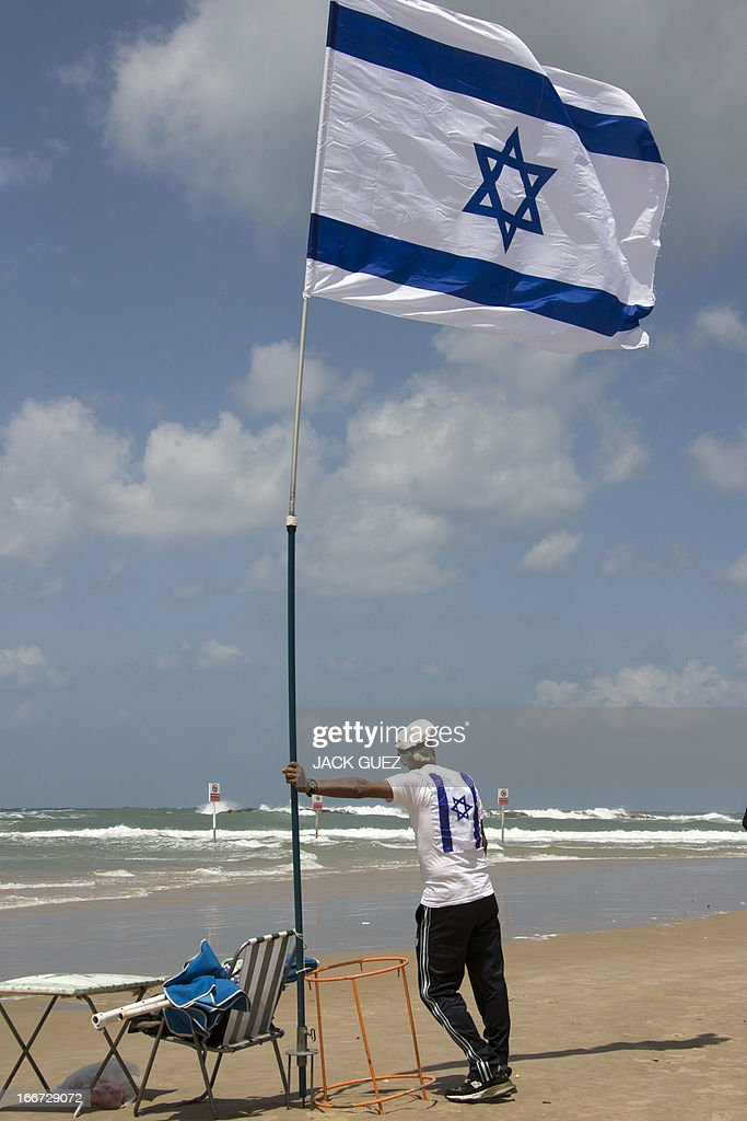 An Israeli man leans up against a flag pole flying his national flag as he watches a military air show on the beach in the Mediterranean coastal city of Tel Aviv, marking the 65th anniversary of Israel's independence on April 16, 2013. Israelis are marking Independence Day, celebrating the 65th year since the founding of the Jewish State in 1948 according to the Jewish calendar. AFP PHOTO/JACK GUEZ