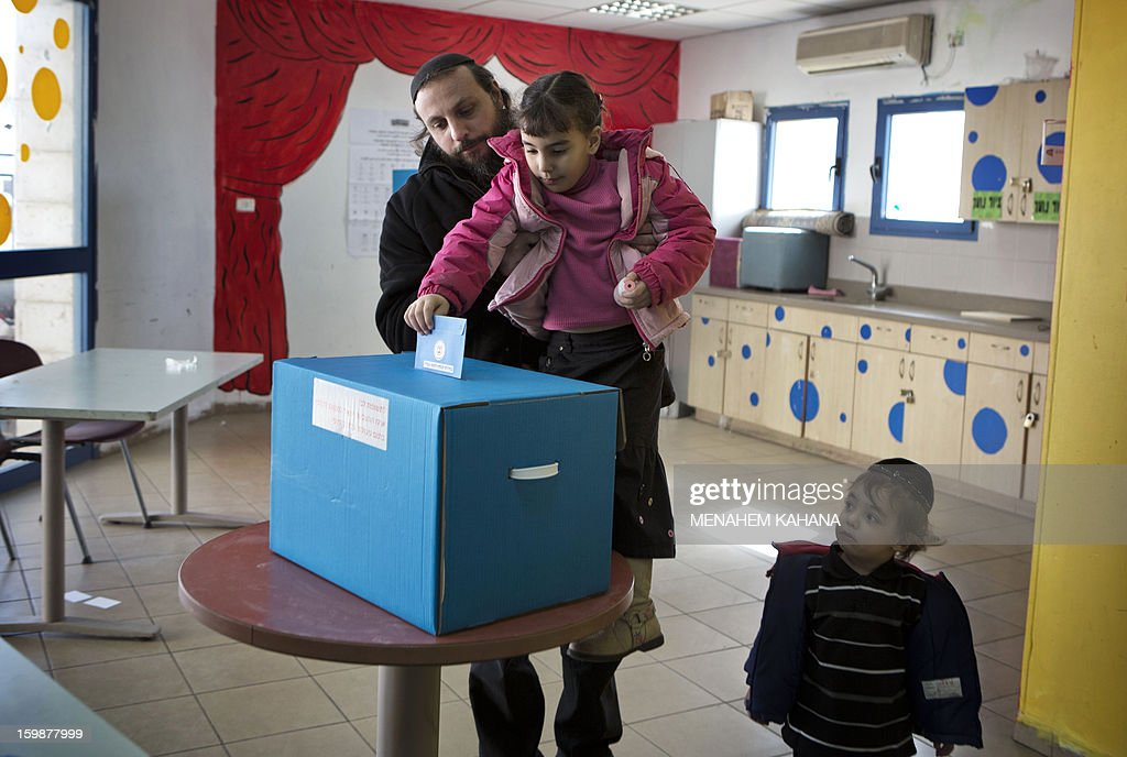 An Israeli man lets his daughter cast his ballot at a polling station in the Jewish settlement of Har Homa in east Jerusalem on January 22, 2013. Voters across Israel and in settlements peppering the occupied West Bank cast ballots for the Israeli general election at more than 10,000 polling stations, with turnout standing at 38.3 percent after seven hours of voting.