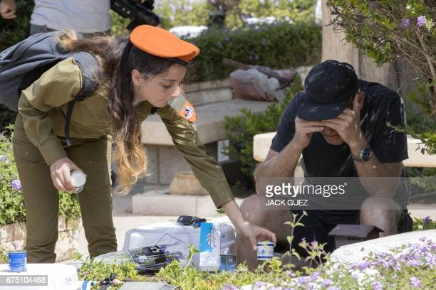 An Israeli man mourns at the grave of a relative at the Kiryat Shaul military cemetery as the country starts to mark the memorial day for fallen...