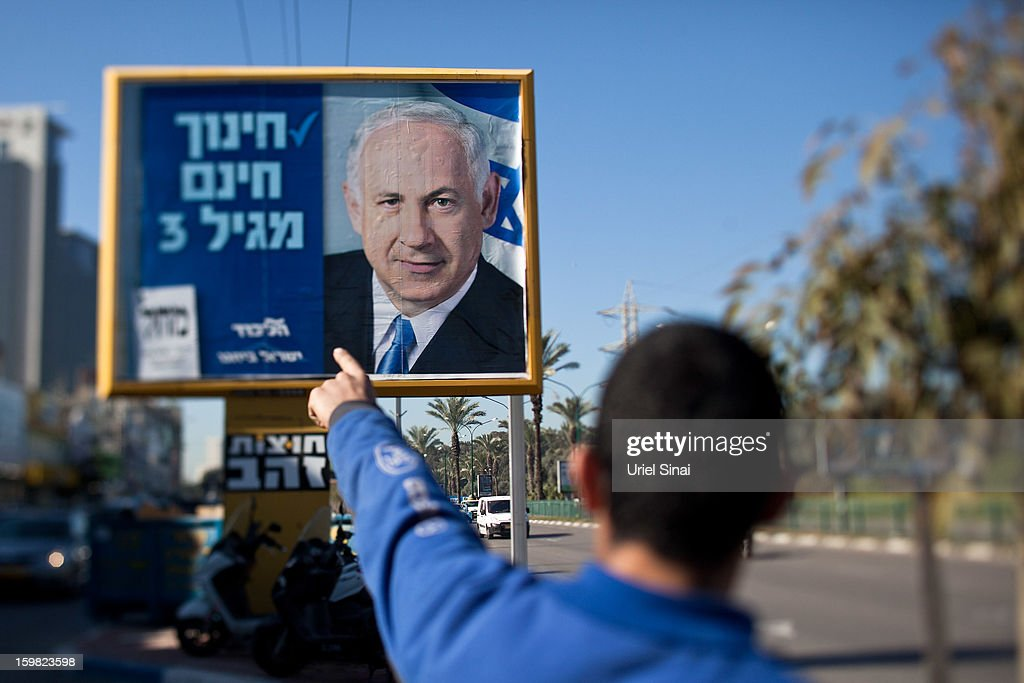 An Israeli man points at a poster of Israeli Prime Minister Benjamin Netanyahu on January 21, 2013 in Tel Aviv, Israel. Israeli elections are scheduled for January 22 and so far showing a majority for the Israeli right.