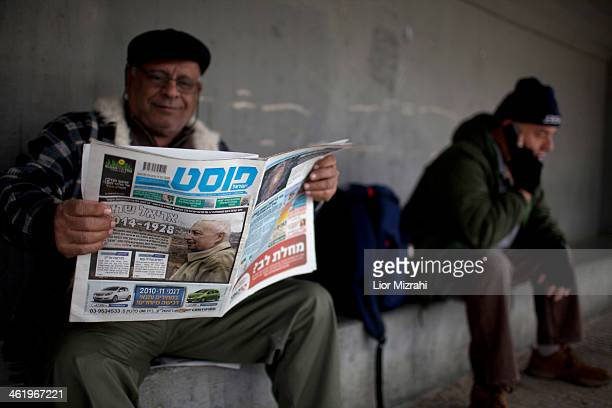 An Israeli man reads a newspaper with a picture of Ariel Sharon as he waits to pay his last respects to Ariel Sharon outside the Knesset where his...