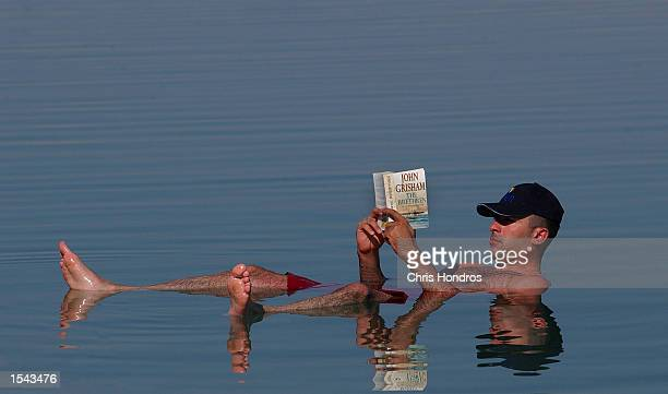 An Israeli man reads a novel while floating May 17 2002 in the Dead Sea in the West Bank Tourism is sharply down in Israel and the West Bank because...
