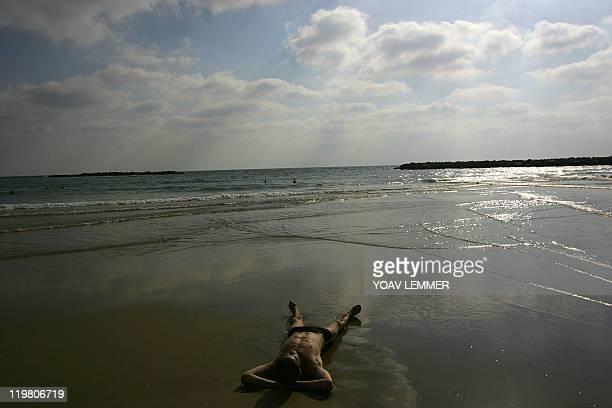 An Israeli man relaxes on a Tel Aviv beach 23 July 2006 as the northern parts of the country came to a halt following constant targeting by the...