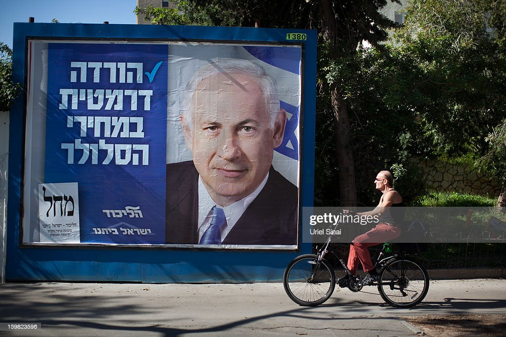 An Israeli man rides his bicycle past a poster of Israeli Prime Minister Benjamin Netanyahu on January 21, 2013 in Tel Aviv, Israel. Israeli elections are scheduled for January 22 and so far showing a majority for the Israeli right.