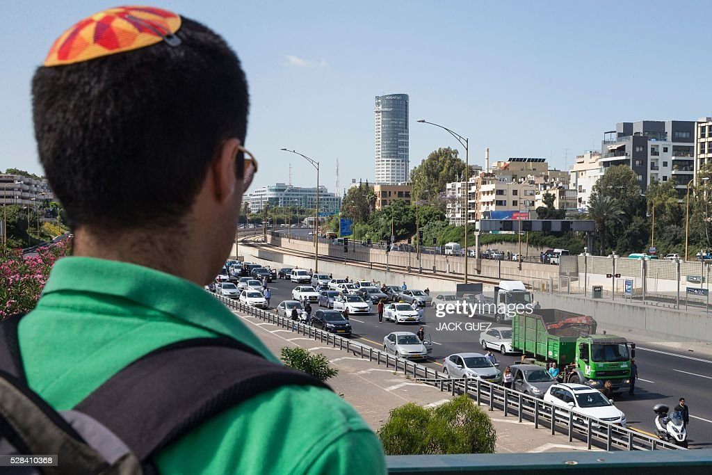 An Israeli man stops and stands in silence as he overlooks a highway in the Israeli city of Tel Aviv on May 5, 2016, as sirens wailed across Israel for two minutes marking the annual day of remembrance for the six million Jewish victims of the Nazi genocide. Israel began marking Holocaust Martyrs and Heroes Remembrance Day at sundown on May 4 with a ceremony at the Yad Vashem memorial museum in Jerusalem, which commemorates the Jews killed by the Nazi regime during World War II. / AFP / JACK