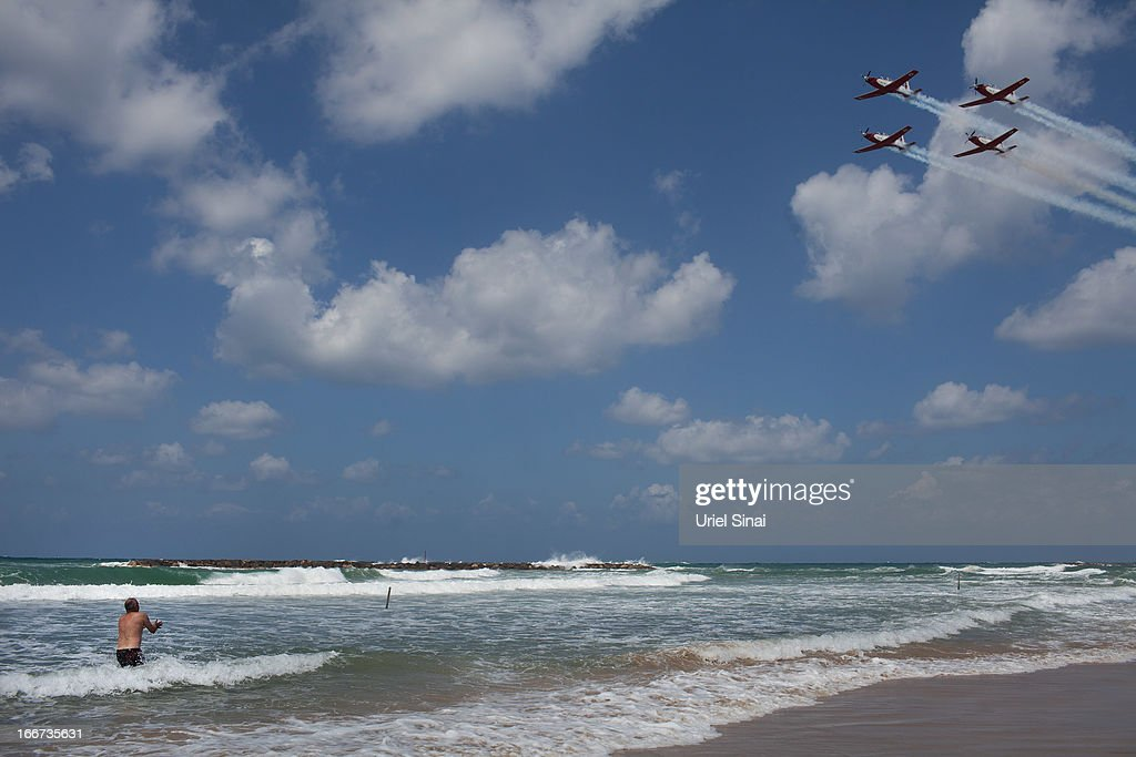 An Israeli man swims in the Mediterranean sea as he watches a military air show marking the 65th anniversary of Israel's independence on April 16, 2013 in Tel Aviv, Israel. The day marks when David Ben-Gurion, the Executive Head of the World Zionist Organization declared the establishment of a Jewish state in Eretz- Israel.