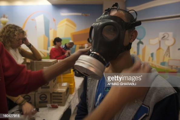 An Israeli man tries on a gas mask from a distribution center at a shopping center in Pisgat Zeev in East Jerusalem on January 31 2013 Syria's...