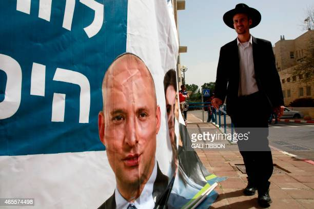 An Israeli man walks past an election campaign poster of Israeli Economy Minister and head of the farright Jewish Home party Naftali Bennett as he...