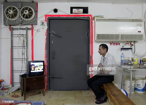 An Israeli man watches the news of Israel's ceasefire with Lebanon on public television while sitting in a bomb shelter during rocket attacks in the...