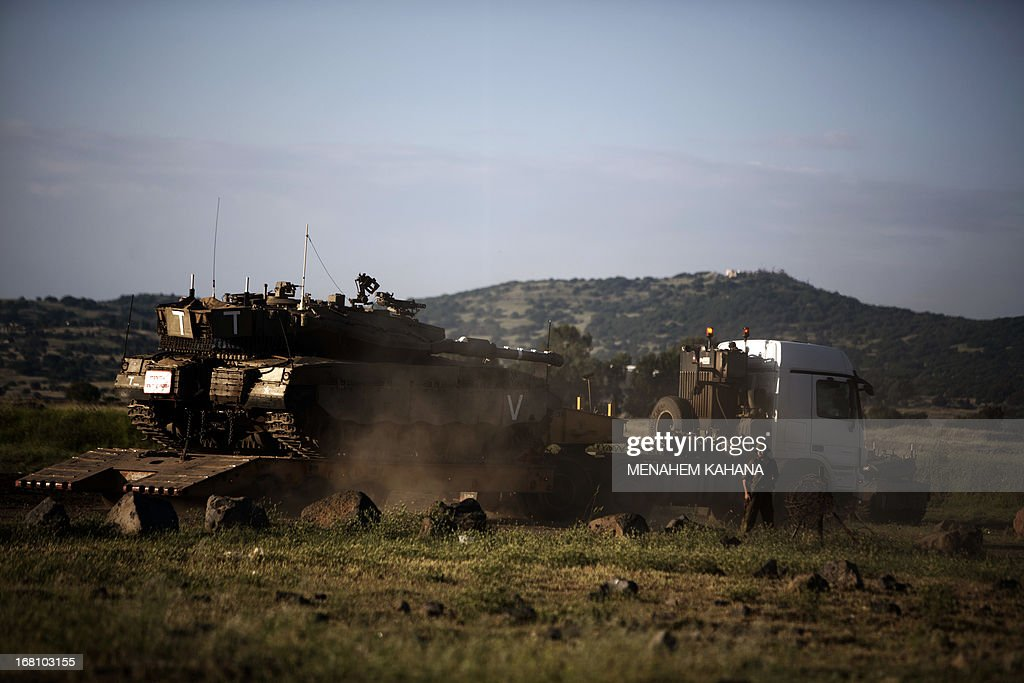 An Israeli Merkava tank is positioned for deployment during a drill in the Israeli annexed Golan Heights near the border with Syria on May 5, 2013. Israel carried out a pre-dawn air strike near Damascus, targeting Iranian missiles destined for Lebanon's Hezbollah in the second such raid on Syria in three days, a senior Israeli source said. AFP PHOTO/MENAHEM KAHANA