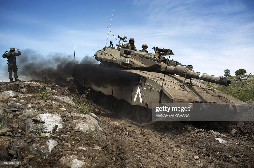 An Israeli Merkava tank maneuvers during a drill in the Israeli annexed Golan Heights near the border with Syria on April 24 2013. Israel's Brigadier General Itai Brun, head of research and analysis in the army's military intelligence division, said that the Damascus regime was guilty of using chemical weapons against rebel fighters.