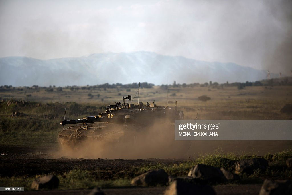 An Israeli Merkava tank maneuvers during a drill in the Israeli annexed Golan Heights near the border with Syria on May 5, 2013. Israel carried out a pre-dawn air strike near Damascus, targeting Iranian missiles destined for Lebanon's Hezbollah in the second such raid on Syria in three days, a senior Israeli source said. AFP PHOTO/MENAHEM KAHANA