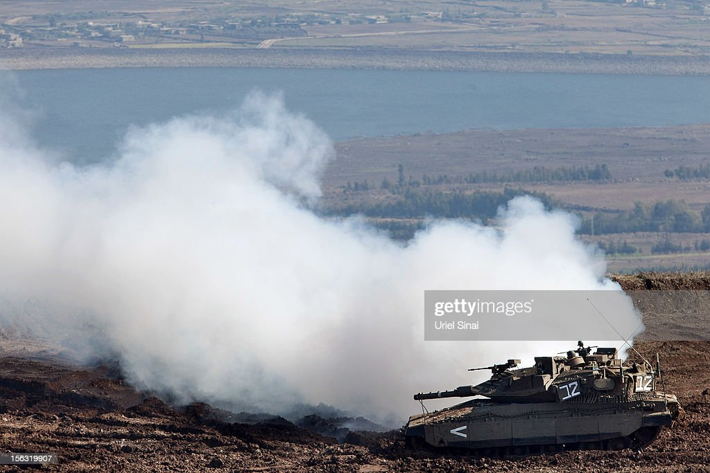An Israeli Merkava tank releases white smoke as it maneuvers on the border line with Syria at the Israeli-annexed Golan Heights, overlooking the Syrian village of Breqa on November 13, 2012 in the Golan Heights. Tension remains high in the disputed Golan Heights after Israeli Defence Forces retaliated after mortar shells were fired into Israeli territory from Syria.