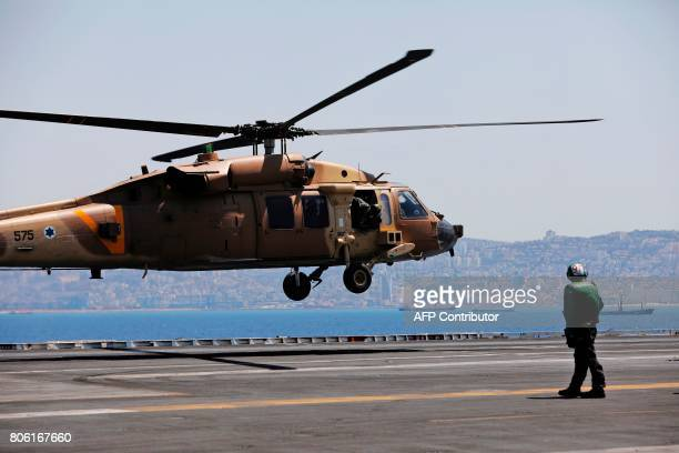 An Israeli military helicopter is seen landing on the US aircraft carrier USS George H W Bush as it docks at the Haifa port Israel July 3 2017 / AFP...