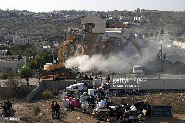 An Israeli municipality worker uses a mechanical shovel to demolish a house belonging to a Palestinian family that was built without municipal...