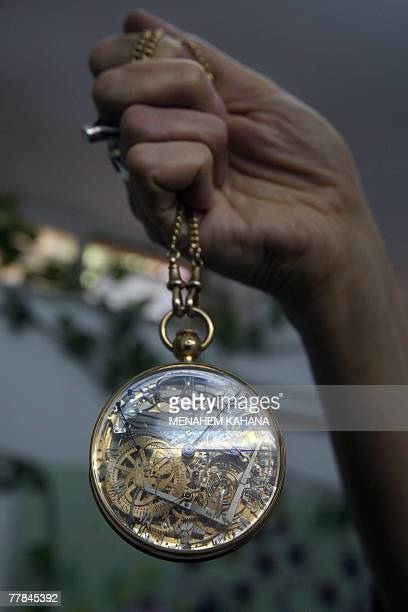An Israeli museum employee holds the recently recovered gold and rockcrystal pocket watch made for the late French queen MarieAntoinette at the...