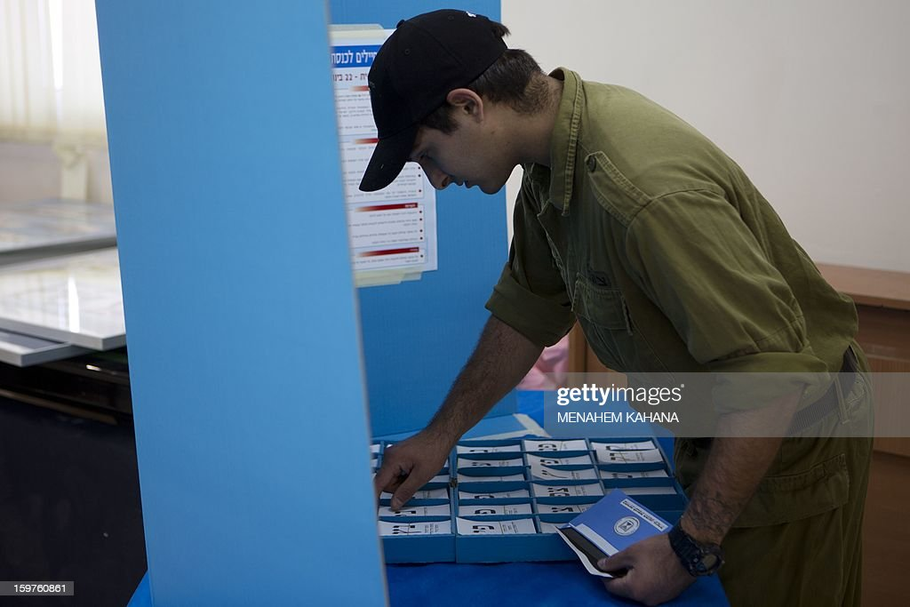 An Israeli Navy soldier takes ballot papers prior to vote at an army Navy base in Ashdod, on January 20, 2013. Israeli soldiers started to vote for the 19th Israeli general election. Thirty-eight parties are running on 34 lists in Israel's general election to be held on January 22. AFP PHOTO/MENAHEM KAHANA