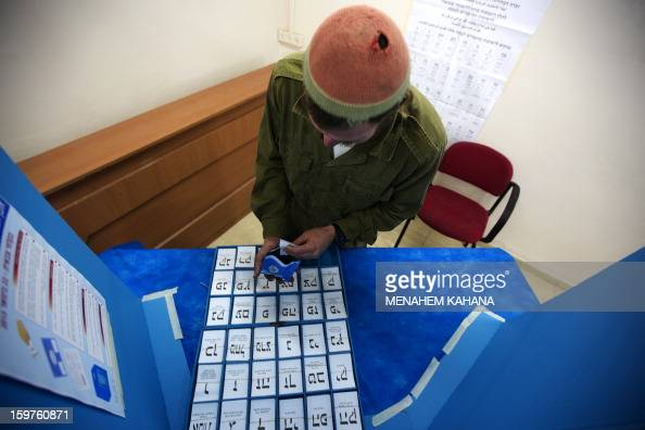 An Israeli Navy soldier takes ballot papers prior to vote at an army Navy base in Ashdod on January 20 2013 Israeli soldiers started to vote for the...