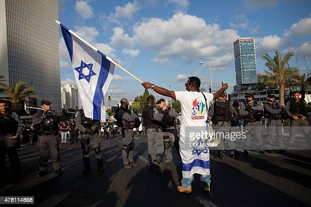 An Israeli of Ethiopian origin with an Israeli flag protests against racism and excessive aggression by Israeli police on June 22 2015 in Tel Aviv...