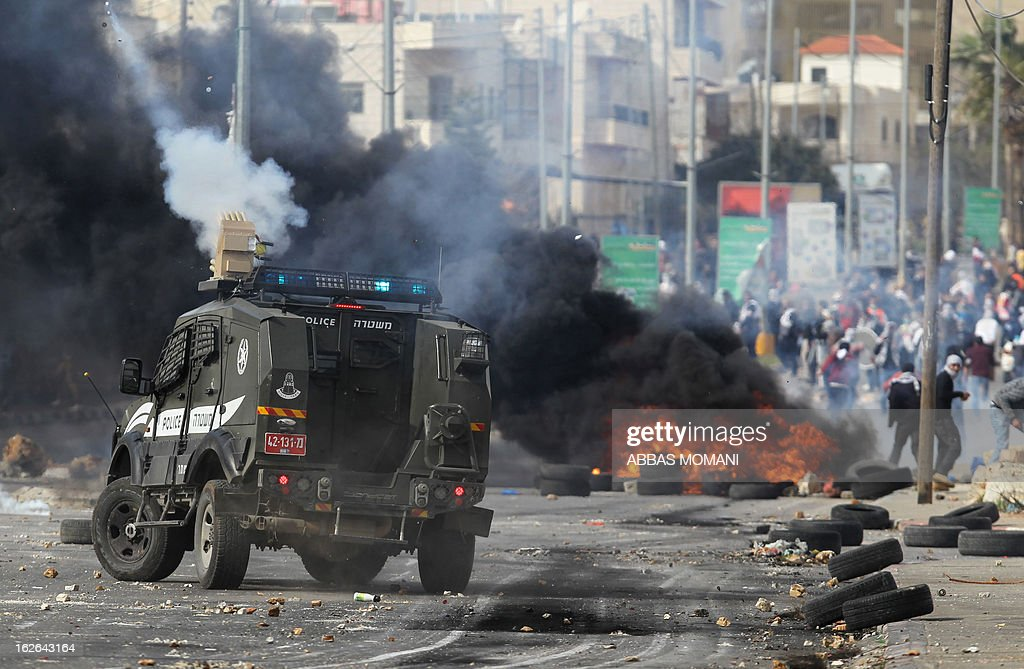 An Israeli police armoured car fires tear gas canisters during clashes with Palestinian youths outside Israel's Ofer prison near Ramallah on February 25, 2013 after a protest in support of Palestinian prisoners on hunger strike in Israeli prisons. Palestinian president Mahmud Abbas said that Israel was deliberately seeking to stoke unrest in the occupied West Bank but that Palestinians would not be provoked.