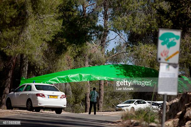 An Israeli police investigator stands at the scene where a body was found on July 2 2014 in Jerusalem IsraelIsraeli Police found a body in a forest...