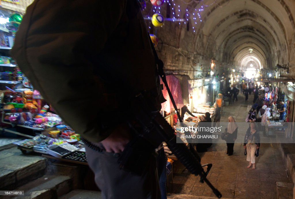 An Israeli police officer stands guard in a lane in the old city of Jerusalem on March 27, 2013. Israeli police stopped a far-right member of parliament, Moshe Feiglin, from entering the flashpoint holy site of the Temple Mount, known to the Palestinians as the al-Aqsa compound, in Jerusalem fearing a violent response from Muslims at the site. AFP PHOTO/AHMAD GHARABLI