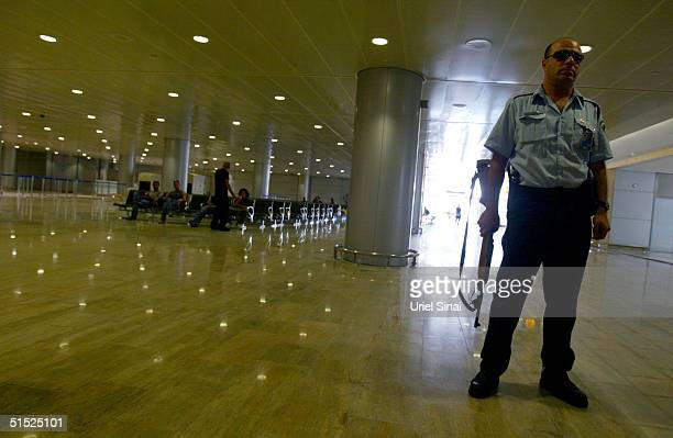 An Israeli police officer stands guard in the departures hall in the new terminal under construction at the Ben Gurion International Airport is seen...