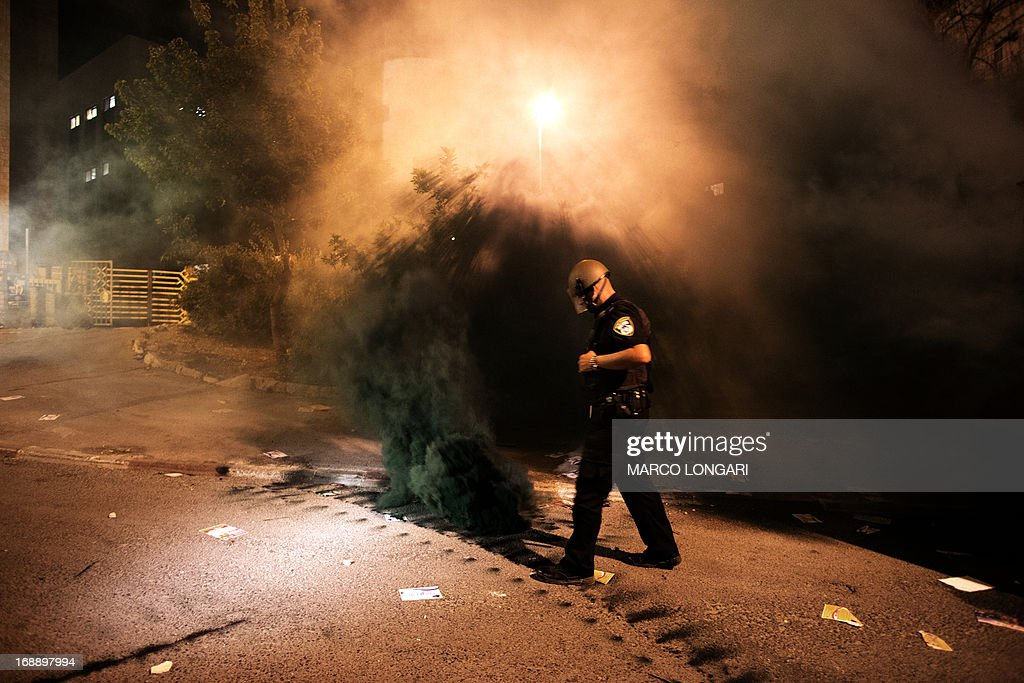 An Israeli police officer tries to put off a smoke grenade thrown by rioting Ultra Orthodox Jews clashing with Israeli police forces in Jerusalem on May 16, 2013, during a protest in front of the main army recruitment office to demonstrate against any plans to make them undergo military service, a police spokesman said. Protesters also prayed and chanted 'the Torah above everything!' referring to Jewish religious law, and 'the army will not take yeshiva (religious seminary) pupils.'